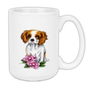 This Cavalier King Charles Spaniel puppy is so sweet as she sits with two pink roses.