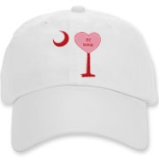 A Candy Heart Palmetto Moon Deluxe Cotton Hat with Be Mine! Perfect for Valentine's Day, it features a pink candy heart on the South Carolina Palmetto Moon with Be Mine.